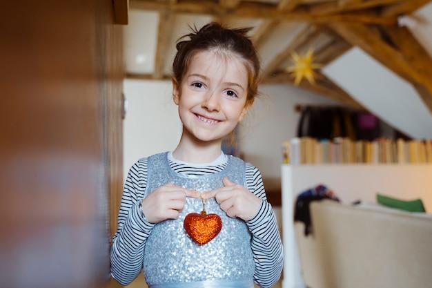 Kleine gild met een saint valentines day-vormige hart in haar borst