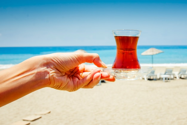 Kleine glazen beker met thee op de achtergrond van de blauwe zee, het strand en parasols.