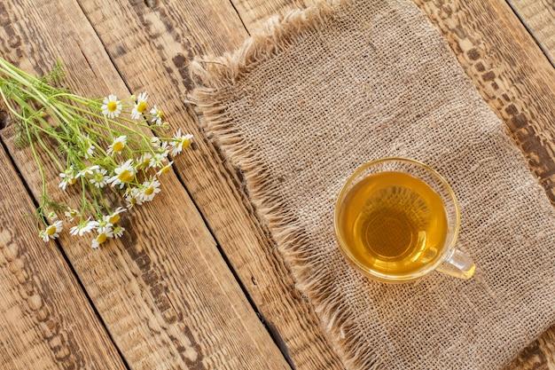 Kleine glazen kom met droge bloemen van matricaria chamomilla op zak en verse witte kamille bloemen op houten achtergrond. bovenaanzicht.