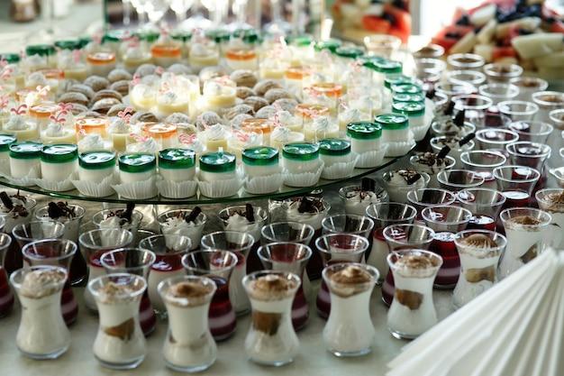 Kleine glazen met koude desserts staan naast elkaar