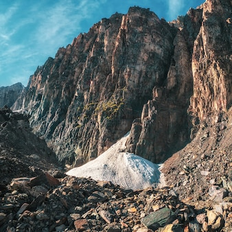 Kleine gletsjer in de grote bergen. rotsachtige bergvallei bij de hoge muur van de bergen. plein uitzicht.