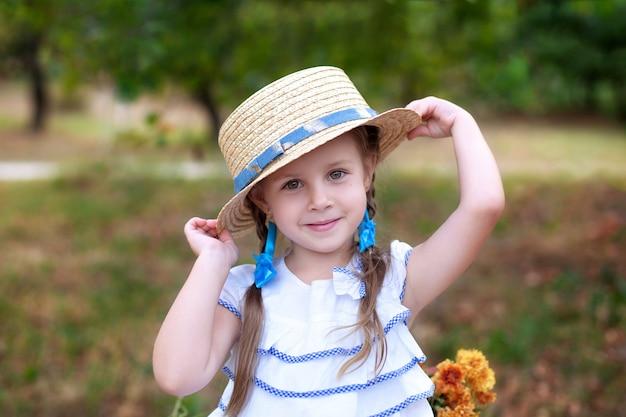 Kleine glimlach meisje met twee pigtails op haar hoofd en in een strooien hoed in de tuin. gelukkig kind en natuur.