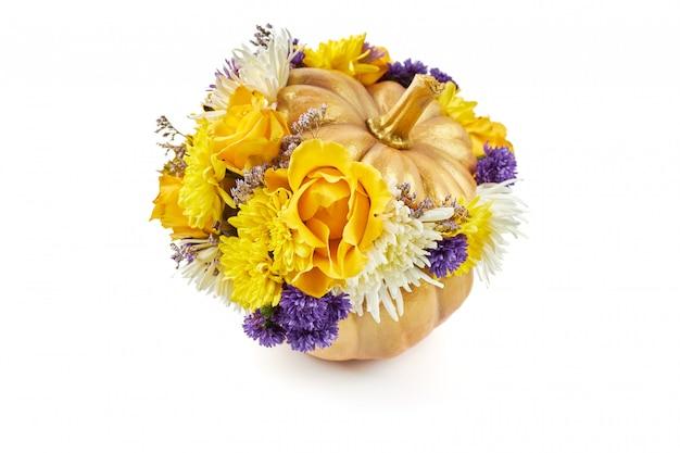 Kleine gouden pompoen versierd met gele en blauwe bloemen als een geschenk op een witte achtergrond