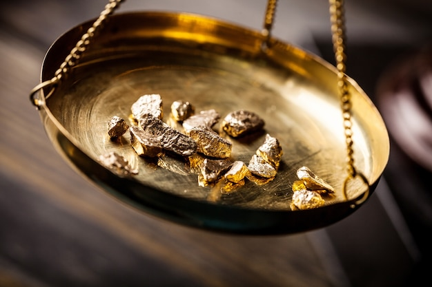 Kleine goudklompjes in een antieke maatschaal