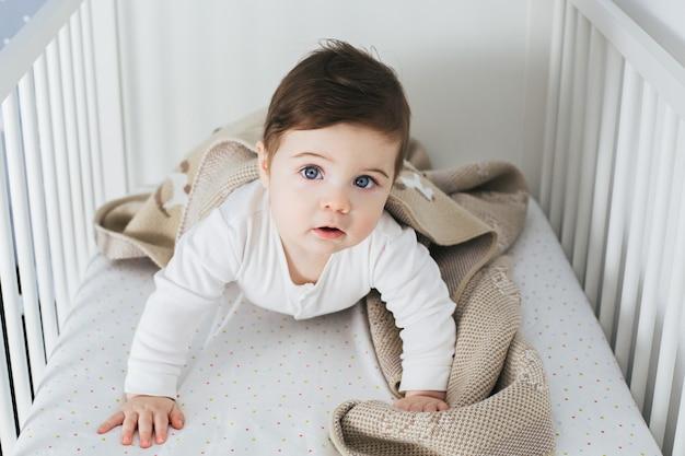 Kleine grappige jongen liggend in een babybed en lachen