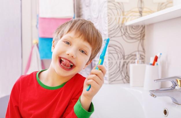 Kleine grappige jongen met een grappige uitdrukking op zijn gezicht in de badkamer