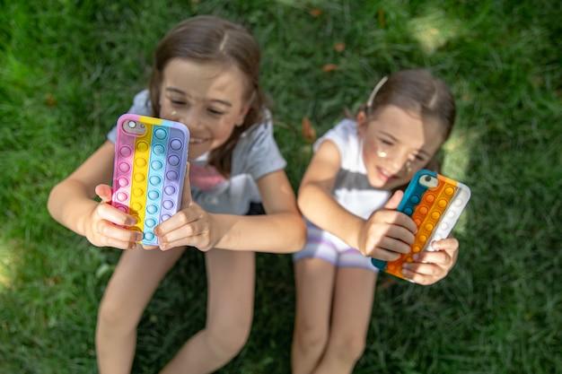 Kleine grappige meisjes op het gras met telefoons in een hoesje met puistjes pop it, een trendy anti-stress speeltje.