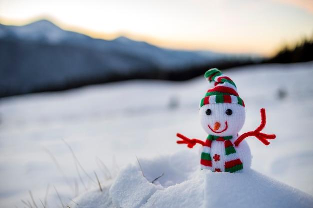 Kleine grappige speelgoed baby sneeuwpop in gebreide muts en sjaal in diepe sneeuw buiten op wazig besneeuwde bergen landschap achtergrond. gelukkig nieuwjaar en merry christmas wenskaart thema.