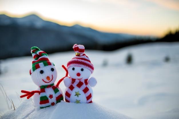Kleine grappige speelgoed baby sneeuwpop in gebreide mutsen en sjaals in diepe sneeuw buitenshuis op wazig bergen landschap