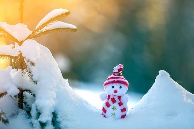 Kleine grappige speelgoed babysneeuwman in gebreide muts en sjaal in diepe sneeuw buiten op helderblauwe en witte kopie ruimte achtergrond. gelukkig nieuwjaar en merry christmas wenskaart.