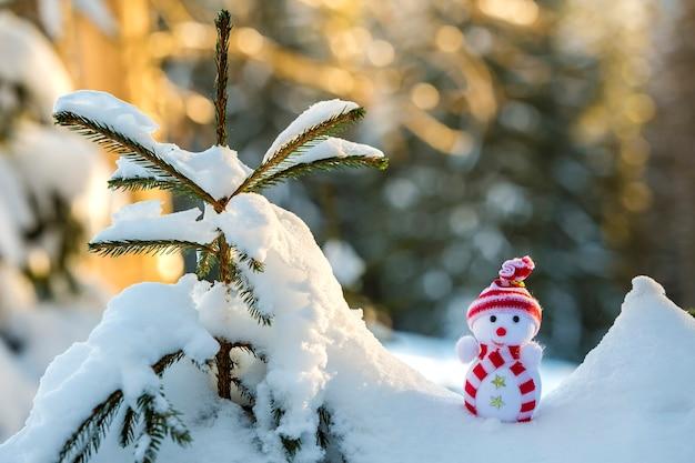 Kleine grappige speelgoed babysneeuwman in gebreide muts en sjaal in diepe sneeuw buiten op heldere blauwe en witte kopie ruimte achtergrond. gelukkig nieuwjaar en merry christmas-wenskaart.