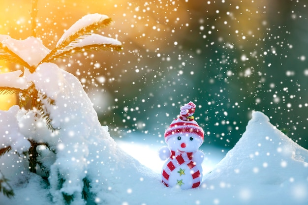 Kleine grappige speelgoed babysneeuwman in gebreide muts en sjaal in diepe sneeuw