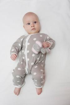 Kleine grappige verraste baby-baby ligt in een jumpsuit met stippen en olifantenknuffel