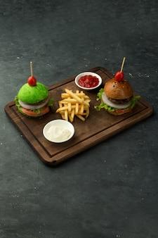 Kleine groene en bruine rundvleesburgers geserveerd met friet, ketchup en mayonaise