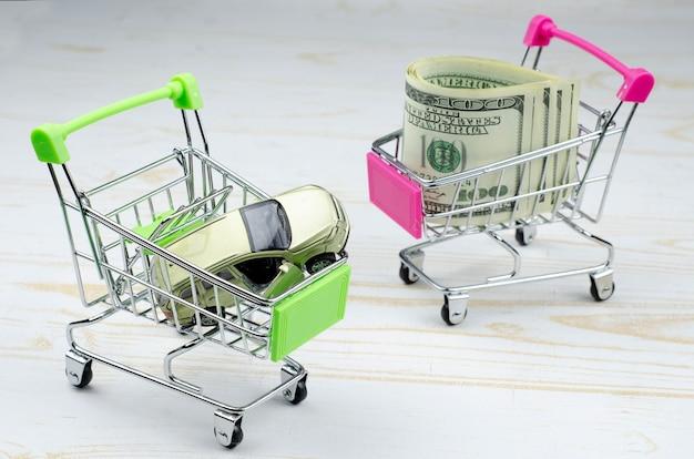 Kleine groene en roze winkelwagentjes met een stuk speelgoed auto en 100 dollarbankbiljetten op wit hout