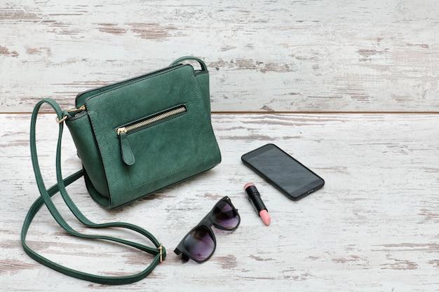 Kleine groene handtas, zonnebril, lippenstift en smartphone