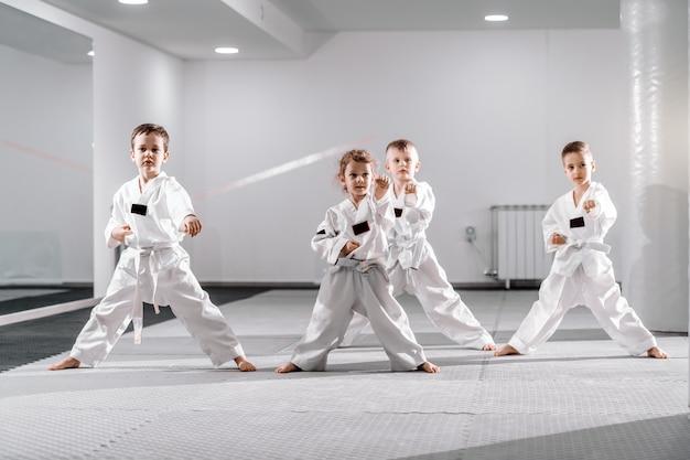 Kleine groep blanke kinderen in doboks die taekwondo oefenen en opwarmen voor treining terwijl ze blootsvoets staan.
