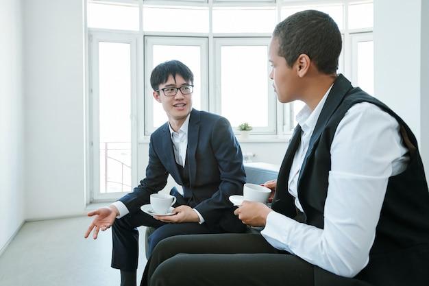 Kleine groep jonge elegante, eigentijdse interculturele zakenpartners in formele kleding die details van rapporten bespreken na de conferentie