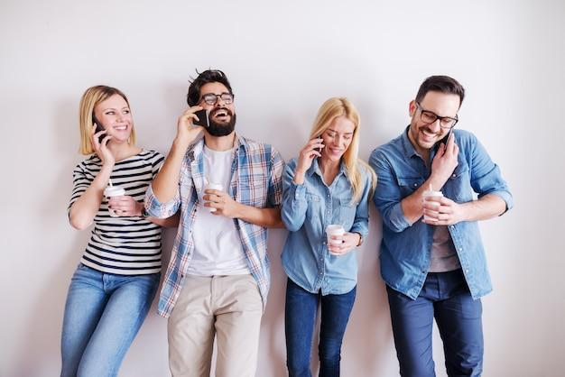 Kleine groep jonge zakenlui die koffie houden om te gaan en slimme telefoons terwijl het spreken en het lachen. op de achtergrond terwijl muur. start bedrijfsconcept.