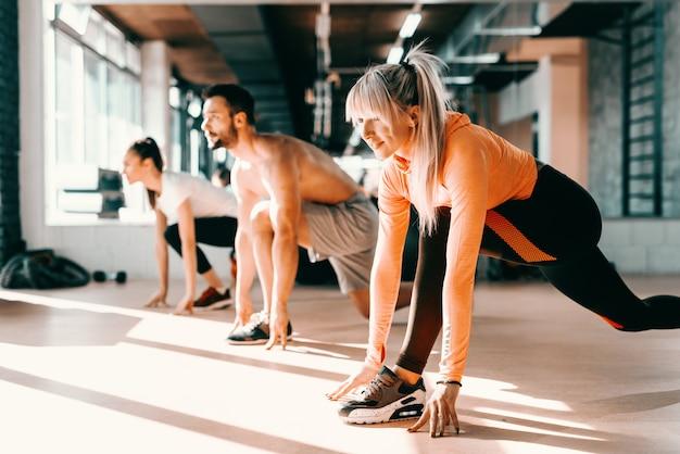 Kleine groep mensen met gezonde gewoonten doen rekoefeningen op een sportschool verdieping. selectieve aandacht op blonde vrouw. in achtergrondspiegel.