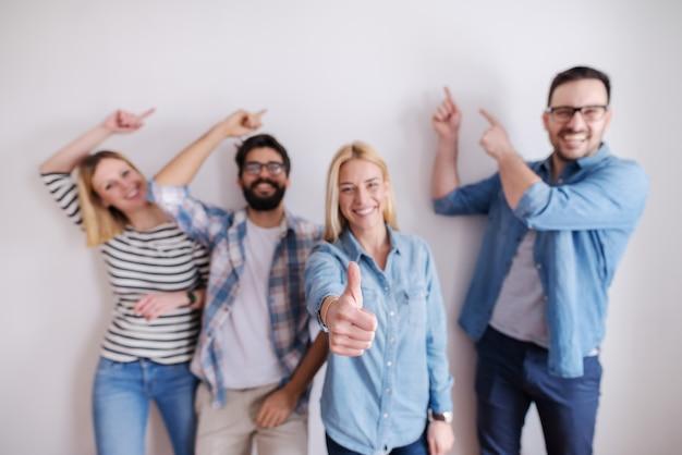 Kleine groep mensen wijzen op de muur en een meisje geeft duimen op. start bedrijfsconcept.