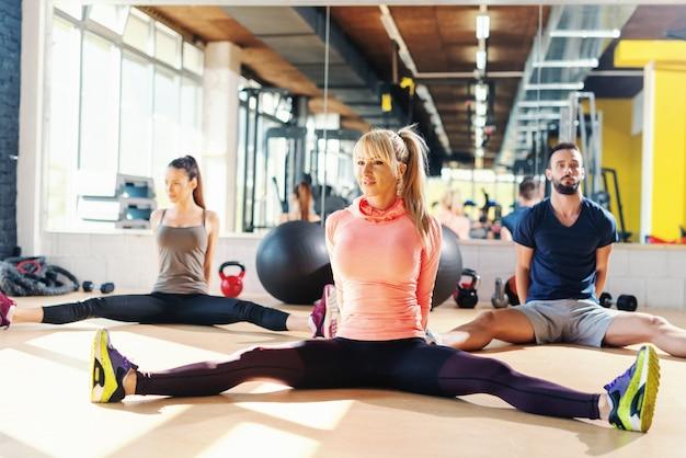 Kleine groep mensen zitten op de sportschool verdieping met gespreide benen.