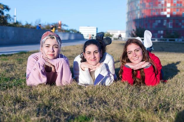 Kleine groep mooie meisjes die samen liggend op gras lachen