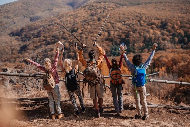 Kleine groep wandelaars handen opstaan en kijken naar prachtig uitzicht.