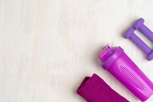 Kleine halters, shaker en handdoek. fitness concept