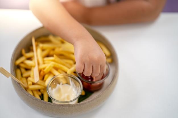 Kleine hand met frietjes dip in tomatenketchup aan tafel