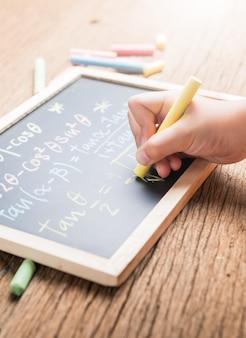 Kleine hand schrijven op een schoolbord