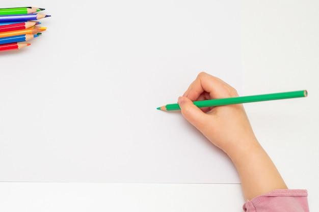 Kleine hand van meisje tekenen op papier.