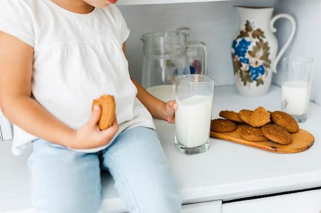 Kleine handen die koekje en een glas melk houden