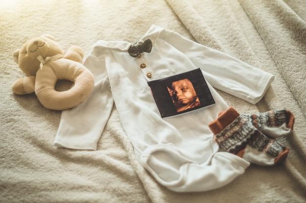 Kleine handgemaakte babykleertjes. foto van echografie. pasgeboren kleding. eenheid, bescherming en geluk