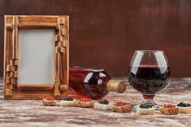 Kleine hapjes met kaviaar en een glas wijn.