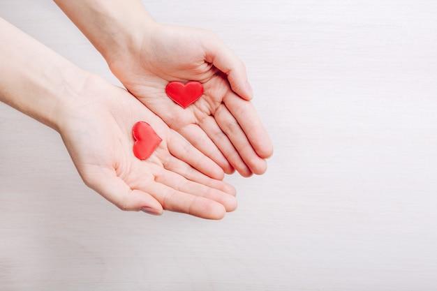 Kleine harten in vrouwelijke handen op lichte houten