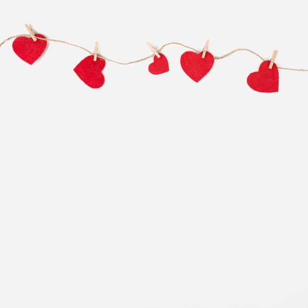 Kleine harten vastgemaakt aan touw op tafel
