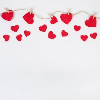 Kleine harten vastgemaakt aan touw op witte tafel