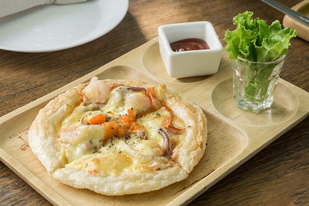 Kleine hawaiiaanse pizza op een houten plaat met tomatensaus in restaurant.