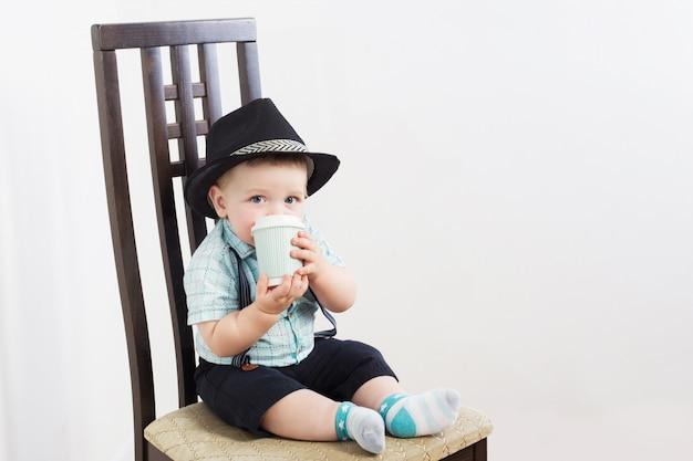 Kleine heer in hoed zit op stoel