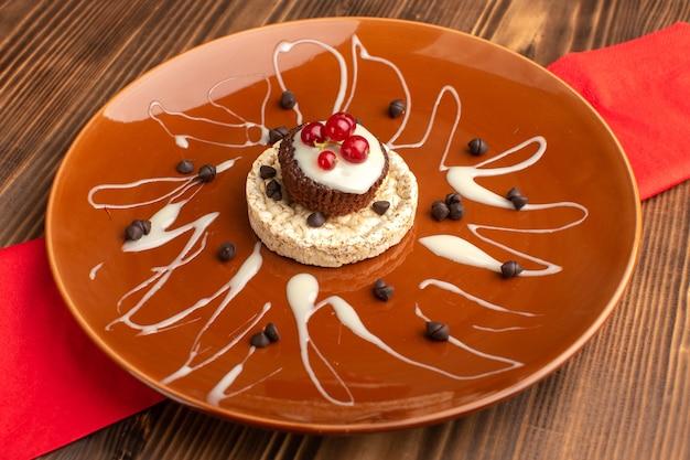 Kleine heerlijke cake met cracker verse veenbessen in bruine plaat op hout