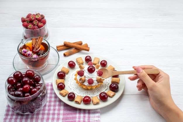 Kleine heerlijke cake met frambozen, kersen en kleine koekjes thee kaneel op licht bureau, fruit bessen cream tea