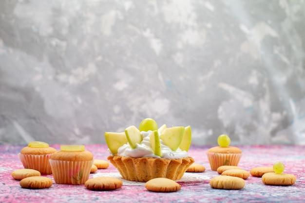 Kleine heerlijke cake met gesneden fruitkoekjes op gekleurd bureau, cake zoete kleurenfoto