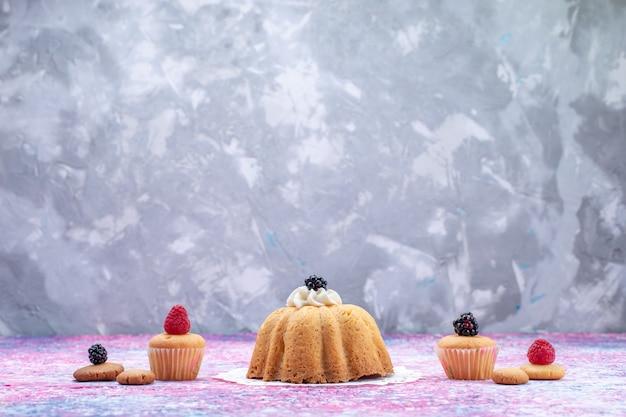 Kleine heerlijke cake met room en bessen op helder bureau, cakekoekje bessen zoete suikerfoto