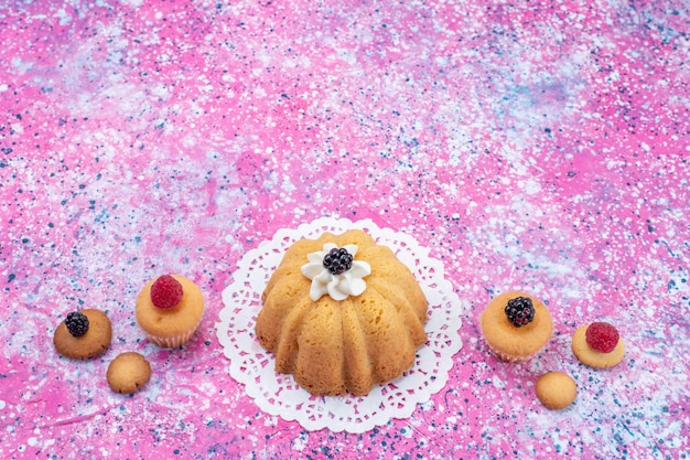 Kleine heerlijke cake met room samen met bessen op een helder bureau, cake biscuit bes zoet