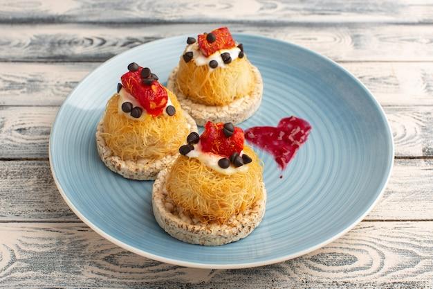 Kleine heerlijke cakes met roomfruit en marmelade bovenop in blauw bord op grijs
