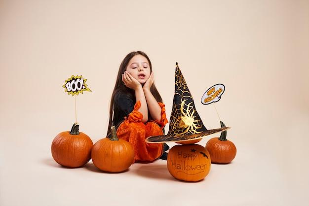 Kleine heks met halloween-pompoen