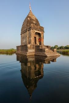Kleine hindoe-tempel in het midden van de heilige rivier de narmada, maheshwar, madhya pradesh staat, india