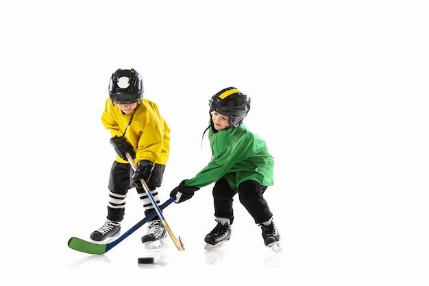 Kleine hockeyspelers met de stokken op ijsbaan en witte studiomuur