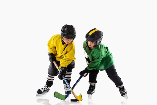 Kleine hockeyspelers met de stokken op ijsbaan en witte studiomuur Gratis Foto